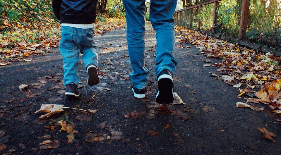 father and son walking in woods