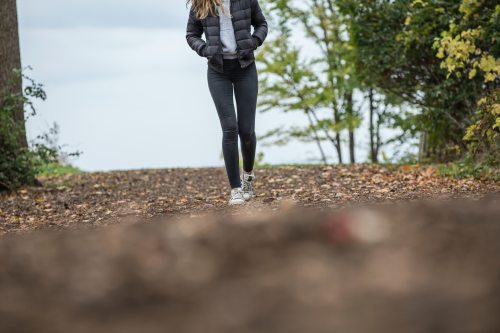 woman-in-black-leggings-while-walking-on-brown-road-663437